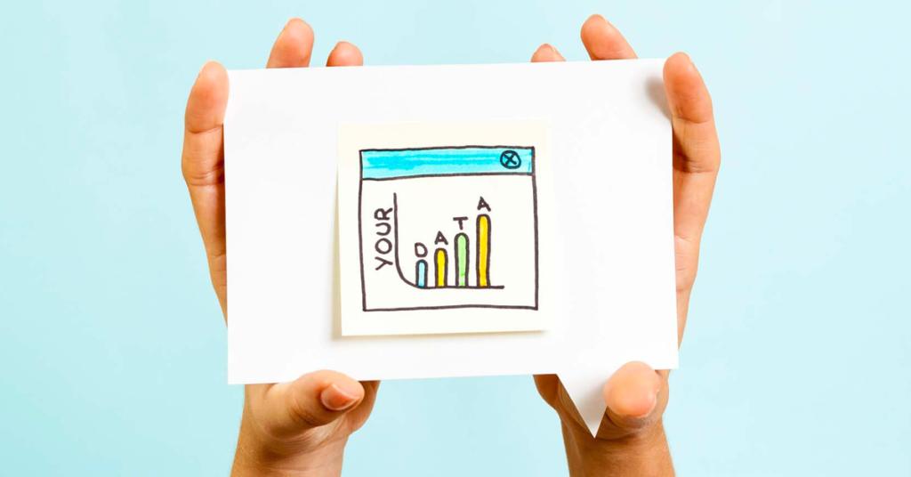Imagem de duas mãos com recorte de papel e gráfico colorido desenhado.